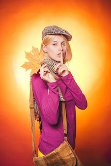 Femme automne tenant la feuille d'or. belle blonde sensuelle jouant avec des feuilles.