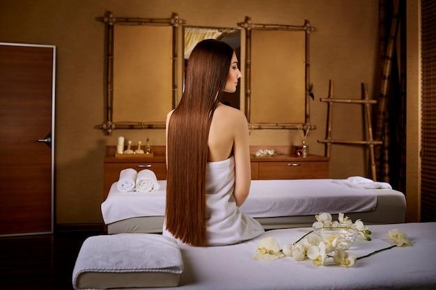 Femme aux beaux cheveux longs assis sur une chaise de massage dans le spa s
