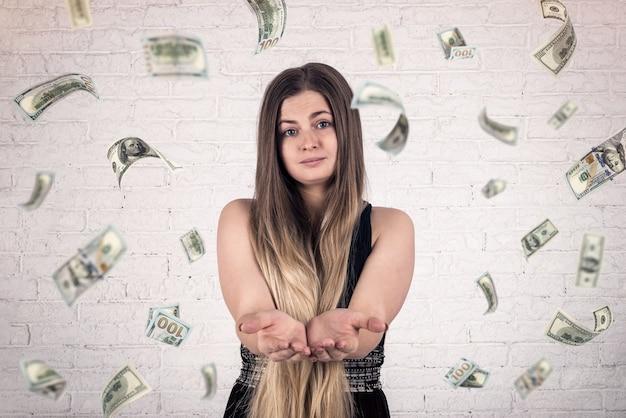 Femme aux bras droits et billets en dollars tombant