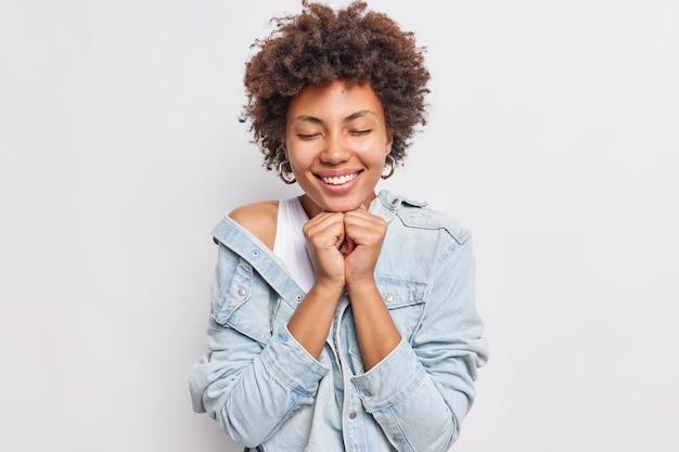 Une femme aux cheveux assez bouclés ferme les yeux sourit largement garde les mains sous le menton a une expression douce porte une veste en jean isolée sur un mur blanc