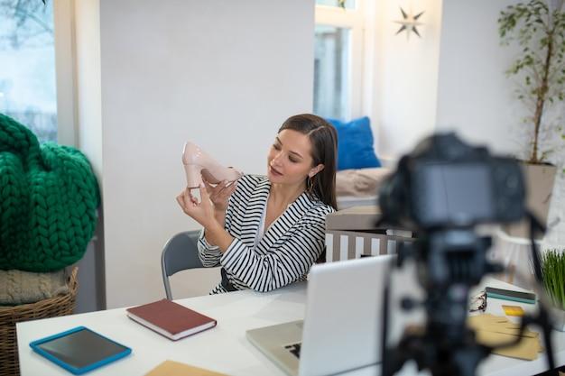 Femme aux cheveux assez longs regardant les chaussures tout en les montrant à ses téléspectateurs sur les réseaux sociaux