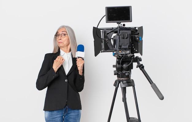 Femme aux cheveux blancs d'âge moyen à l'air arrogante, réussie, positive et fière et tenant un microphone. concept de présentateur de télévision