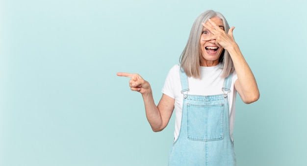 Femme aux cheveux blancs d'âge moyen ayant l'air choquée, effrayée ou terrifiée, couvrant le visage avec la main et pointant vers le côté