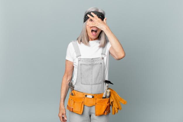 Femme aux cheveux blancs d'âge moyen ayant l'air choquée, effrayée ou terrifiée, couvrant le visage avec la main et portant des vêtements de travail et des outils. concept de ménage