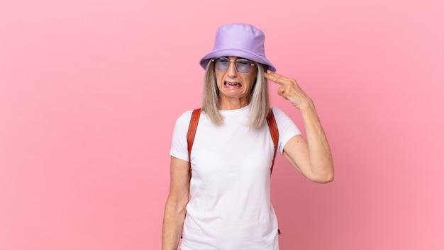 Femme aux cheveux blancs d'âge moyen ayant l'air malheureuse et stressée, geste de suicide faisant signe d'arme à feu. concept d'été
