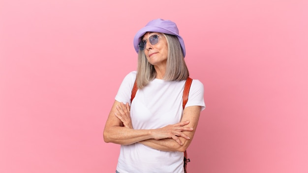 Femme aux cheveux blancs d'âge moyen haussant les épaules, se sentant confuse et incertaine