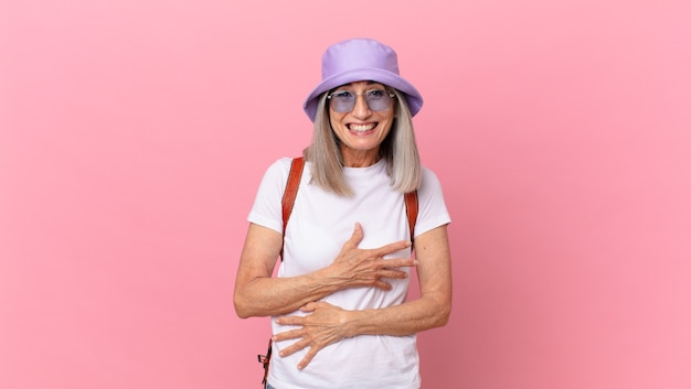 Femme aux cheveux blancs d'âge moyen riant aux éclats d'une blague hilarante. concept d'été