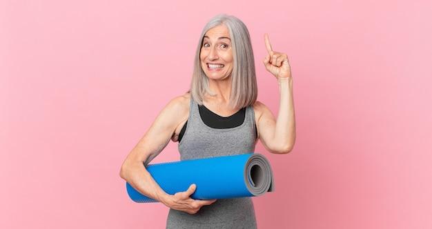 Femme aux cheveux blancs d'âge moyen se sentant comme un génie heureux et excité après avoir réalisé une idée et tenant un tapis de yoga. concept de remise en forme
