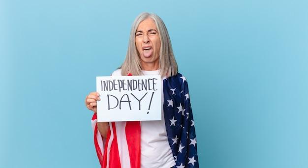 Femme aux cheveux blancs d'âge moyen se sentant dégoûtée et irritée et tirant la langue. concept de la fête de l'indépendance