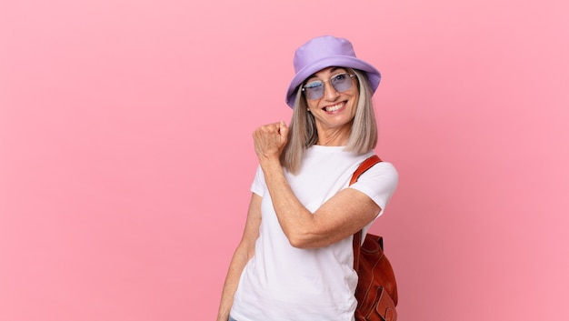 Femme aux cheveux blancs d'âge moyen se sentant heureuse et confrontée à un défi ou à la célébration. concept d'été