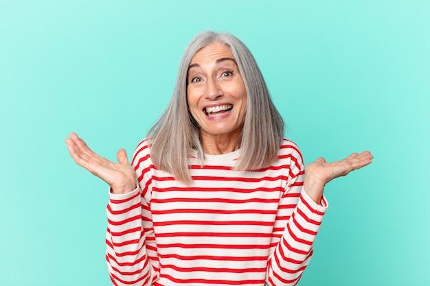 Femme aux cheveux blancs d'âge moyen se sentant heureuse et étonnée de quelque chose d'incroyable