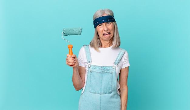 Femme aux cheveux blancs d'âge moyen se sentant perplexe et confuse avec un rouleau peignant un mur