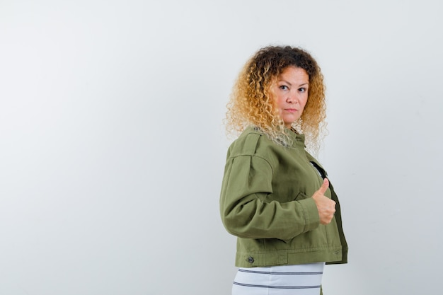 Femme aux cheveux blonds bouclés montrant le pouce vers le haut en veste verte et à la confiance. vue de face.