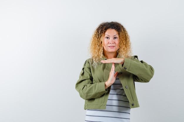Femme aux cheveux blonds bouclés en veste verte montrant le geste de pause et à la perplexité, vue de face.