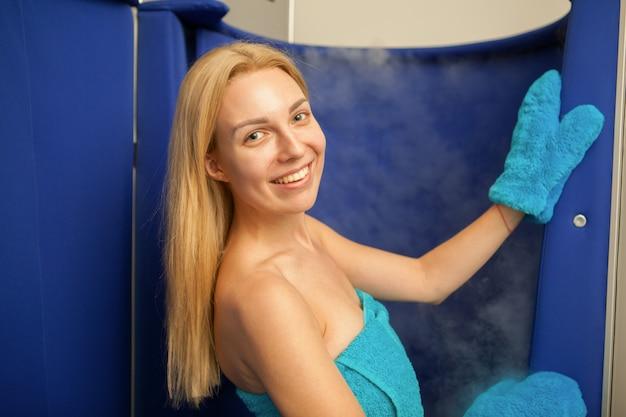 Femme aux cheveux blonds entrant dans la cabine de sauna de cryothérapie