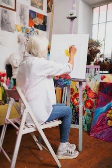 Femme aux cheveux blonds. femme aux cheveux blonds avec coupe bob portant des baskets alors qu'il était assis près de toile et de peinture