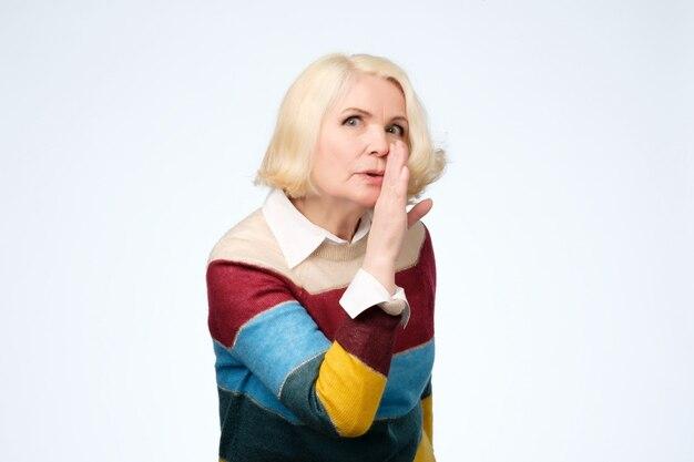 Une femme aux cheveux blonds habillée dit des nouvelles secrètes de freinage à chaud