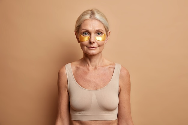 Une femme aux cheveux blonds peignés utilise des patchs dorés sous les yeux