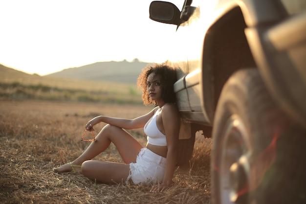 Femme aux cheveux bouclés assis à côté de la voiture sur un champ d'herbe