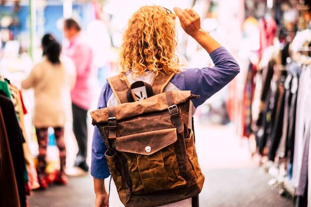 Femme aux cheveux bouclés blonds backpacker traveler vu de l'arrière au marché d'occasion profitant du shopping et des vacances alternatives