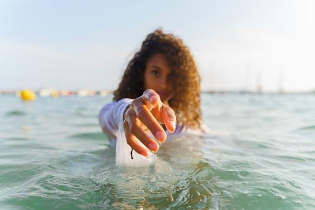 Femme aux cheveux bouclés debout dans la mer et pointant avec sa main