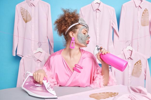 Femme aux cheveux bouclés détient un spray détergent occupé avec un masque d'argile.