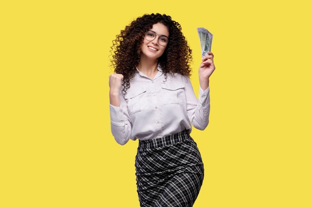 Femme aux cheveux bouclés du caucase détient des billets en dollars en argent célébrant la victoire et le succès très excité avec bras levé