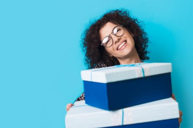 Femme aux cheveux bouclés du caucase sourit à l'avant avec des lunettes tout en tenant des boîtes présentes sur un mur bleu avec un espace libre