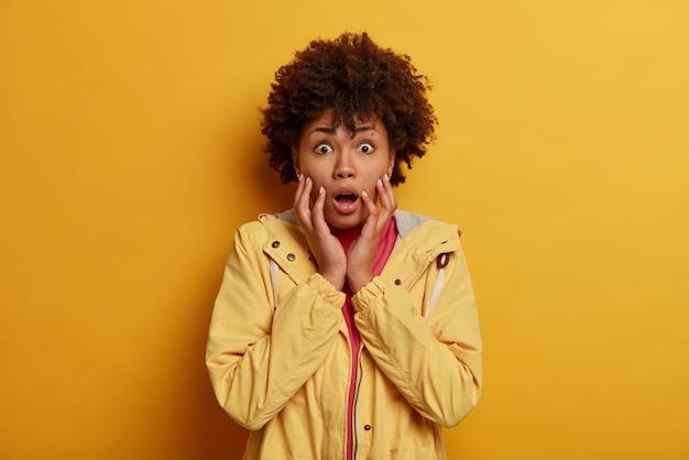Une femme aux cheveux bouclés effrayée et effrayée halète de peur, tremble et reste horrifiée, déçue et inquiète des mauvaises conséquences