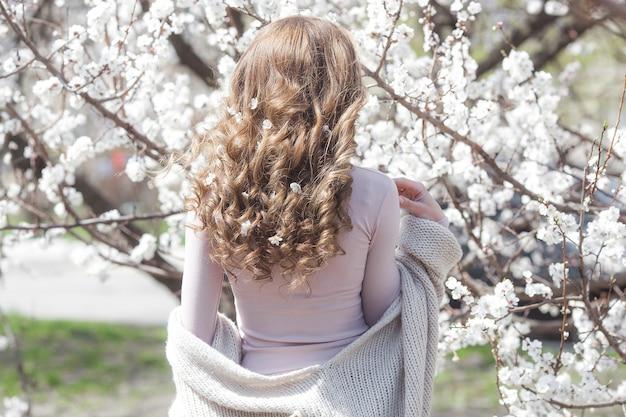 Femme aux cheveux bouclés à l'extérieur sur fond de printemps. dame méconnaissable aux cheveux blonds et longs en bonne santé. coupe de cheveux fille gros plan encore