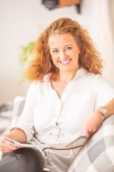 Une femme aux cheveux bouclés lit un magazine, assise sur un canapé dans un salon, souriant à la caméra.