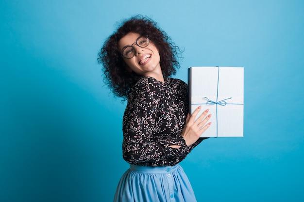 Femme aux cheveux bouclés avec des lunettes portant une robe présente à la caméra une boîte avec cadeau posant sur un mur de studio bleu