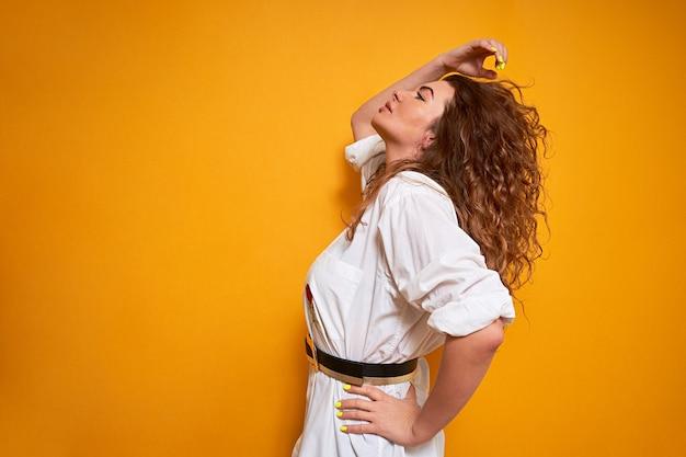 Une femme aux cheveux bouclés luxuriants se tient sur le côté. elle retient ses cheveux d'une main, les redresse et détourne le regard.
