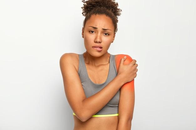 Femme aux cheveux bouclés mécontente mord les lèvres, touche l'épaule douloureuse, souffre d'une blessure, porte un haut gris, isolé sur fond blanc. problèmes de santé, concept médical
