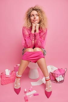 Une femme aux cheveux bouclés à la mode est assise confortablement sur la cuvette des toilettes garde les mains sous le menton considère quelque chose tout en déféquant profite d'une atmosphère domestique confortable entourée de différentes choses féminines
