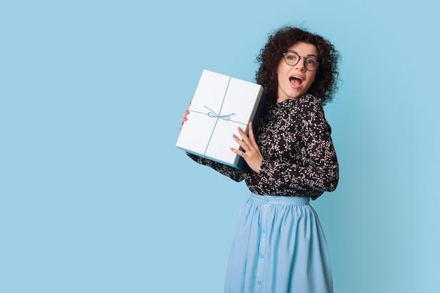 Femme aux cheveux bouclés montre à l'avant une boîte présente posant joyeusement près de l'espace libre bleu