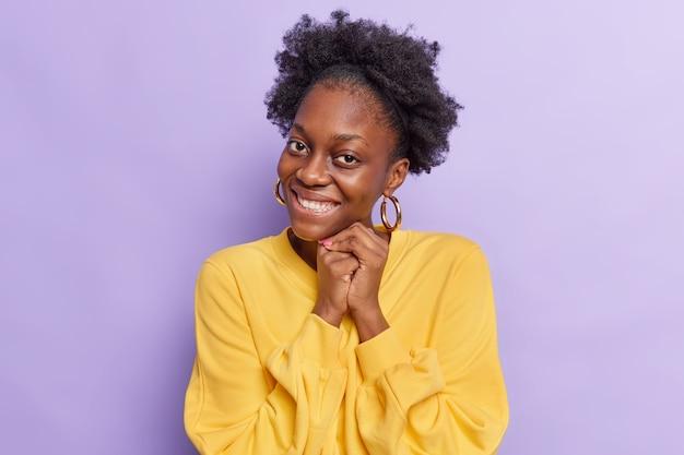 Une femme aux cheveux bouclés naturels garde les mains ensemble près du visage sourit à pleines dents se sent touchée porte un pull jaune décontracté isolé sur violet