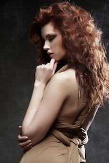 Femme aux cheveux bouclés rouge vif