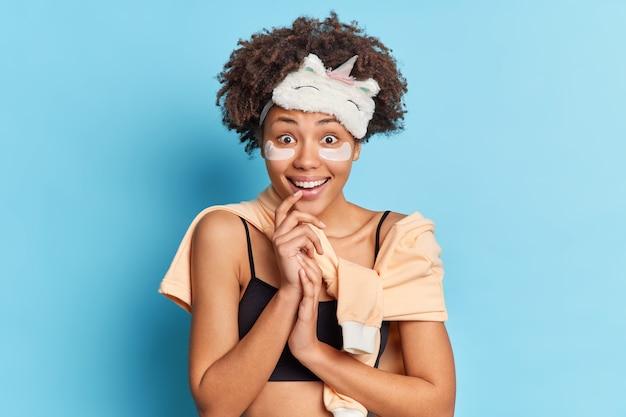 Femme aux cheveux bouclés sourit agréablement vêtue de vêtements de nuit concentrés entend heureusement d'excellentes nouvelles isolé sur mur bleu