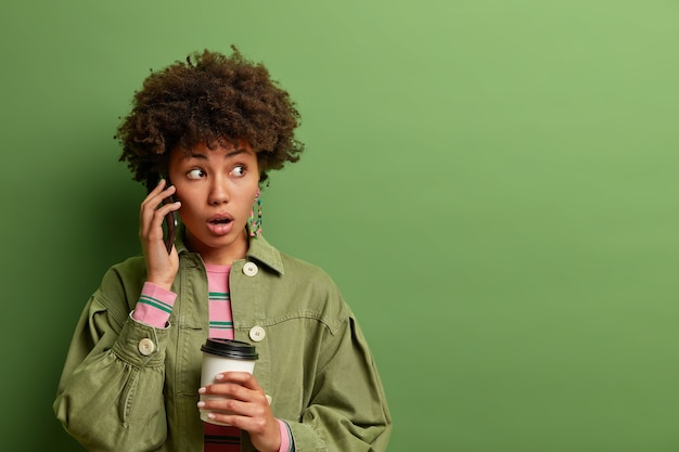 Femme aux cheveux bouclés surpris émotionnel tient le smartphone près de l'oreille, regarde avec une expression choquée, détient une tasse de café jetable, porte des vêtements à la mode,