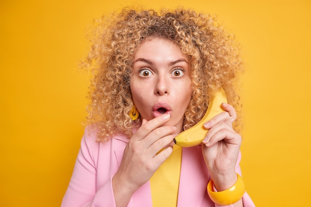 Une femme aux cheveux bouclés surprise tient une banane mûre fraîche près de l'oreille prétend appeler garde la bouche ouverte d'étonnement vêtue de vêtements formels pose contre un mur jaune vif. réaction humaine