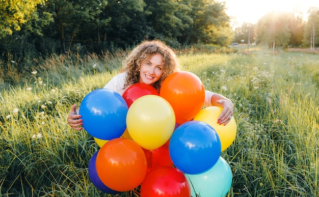 Une femme aux cheveux bouclés tient des ballons arc-en-ciel dans ses mains. jeune belle fille sur l'herbe dans le parc.