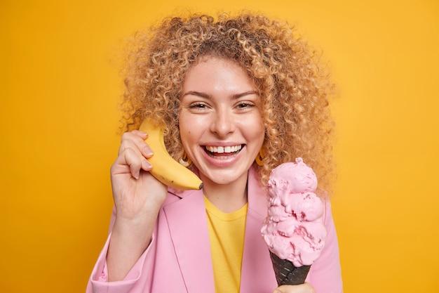 Une femme aux cheveux bouclés tient une délicieuse banane près de l'oreille appelle un ami mange une délicieuse crème glacée a une humeur optimiste sourit largement