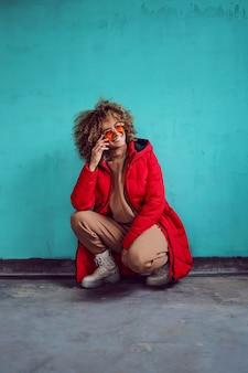 Femme aux cheveux bouclés, en veste rouge accroupie devant le mur et en détournant les yeux.