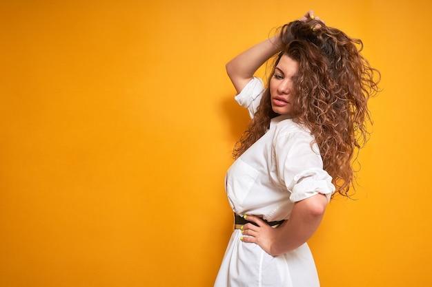 Une femme aux cheveux bouclés volumineux se tient sur le côté. elle tient ses cheveux d'une main, les redresse et détourne le regard.