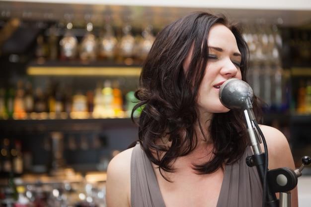 Femme aux cheveux brune chantant dans un micro