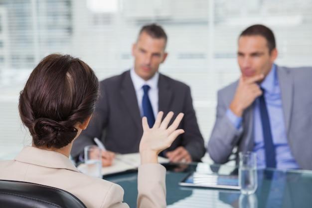 Femme aux cheveux brune parle à ses interviewers