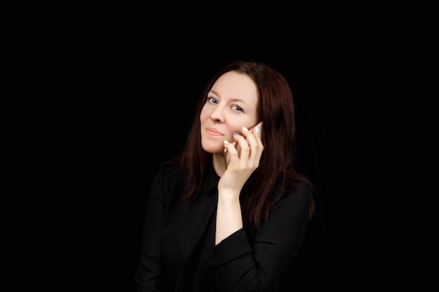 Femme aux cheveux bruns d'âge moyen parle au téléphone avec émotion.