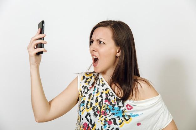 La femme aux cheveux bruns en colère parle au téléphone mobile sur fond blanc. notion d'émotions.
