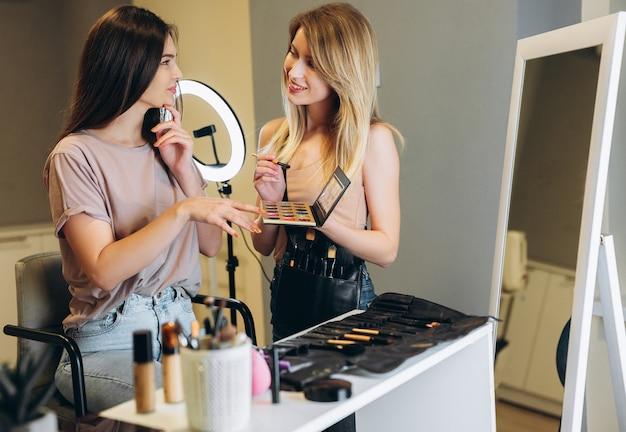 Une femme aux cheveux bruns pointe du doigt la couleur de fard à paupières sélectionnée. maquilleuse et cliente choisissent la couleur du fard à paupières.